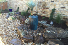 Pot fountain incased with boulders and river rock